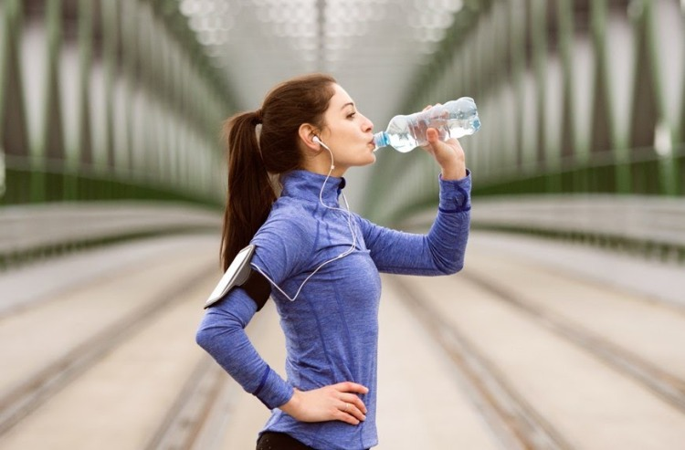 GettyImages-woman-drinking-water-workout-Halfpoint